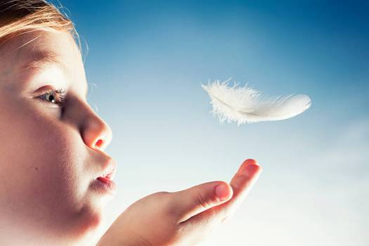 Conceptual close up of a little girl blowing a bird feather away.